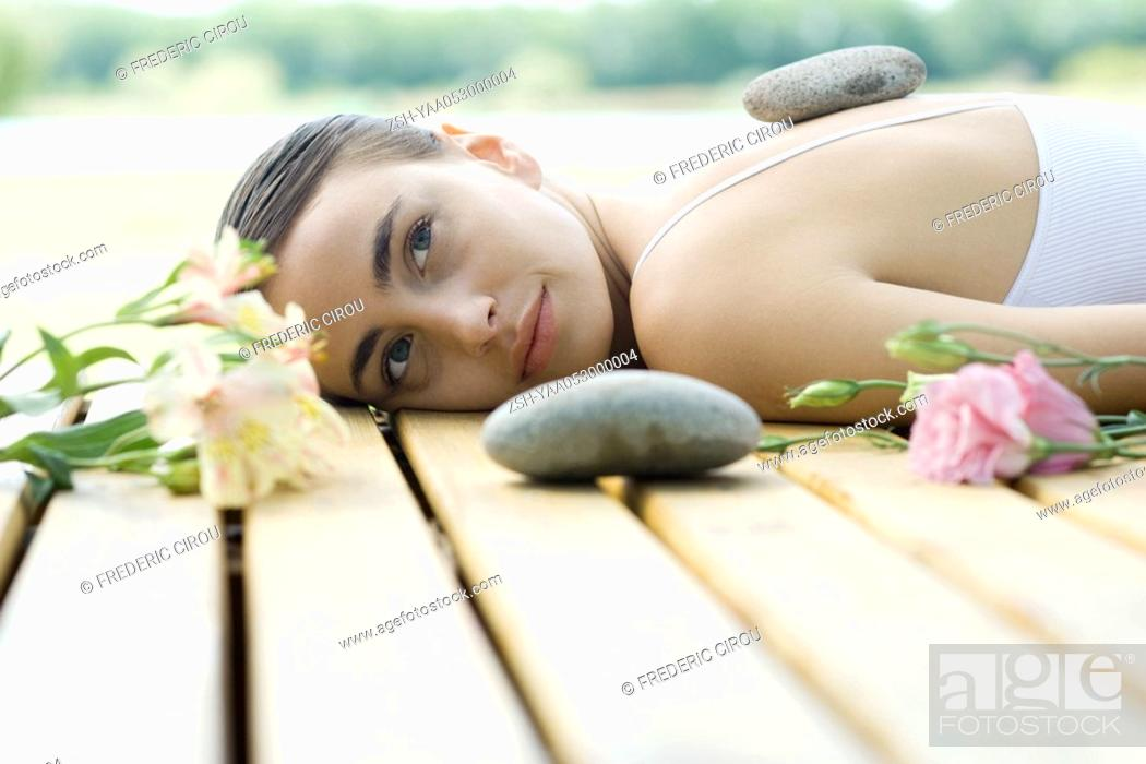 Stock Photo: Woman lying on deck with hot stone on back surrounded by flowers and stones.