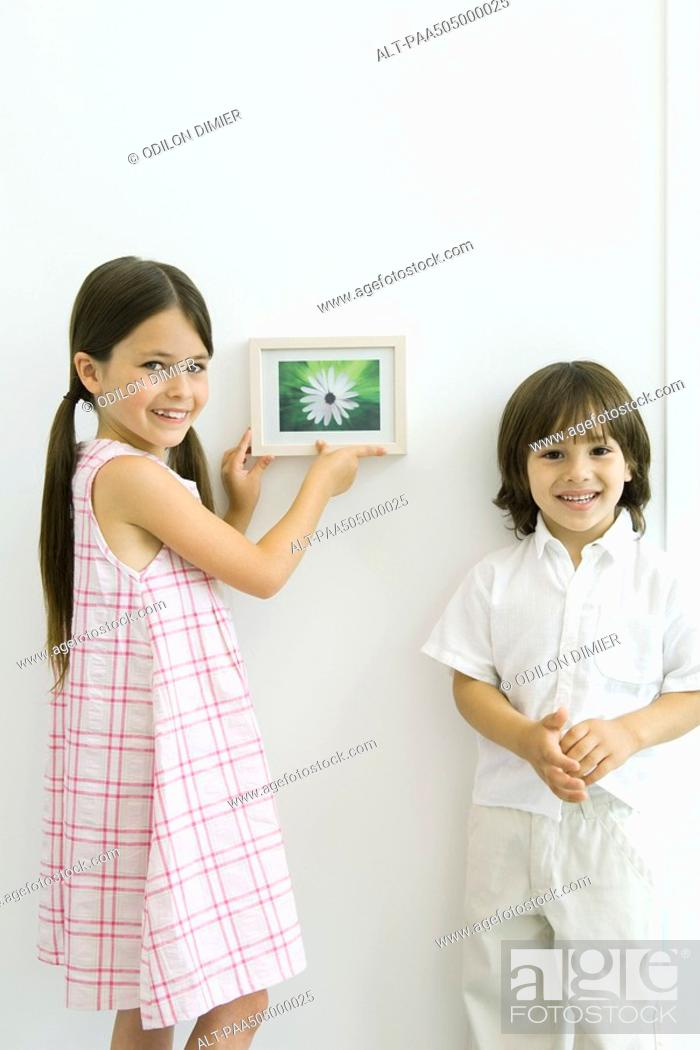 Stock Photo: Girl standing beside younger brother, hanging framed picture, both smiling at camera.