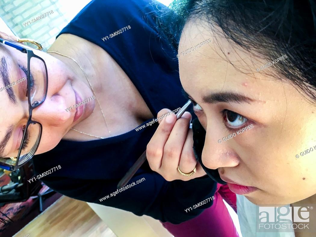 Stock Photo: Tilburg, Netherlands. Young womna from the Dutch Antilles doing the make up of a young, Chinese woman, just before a photo shoot.