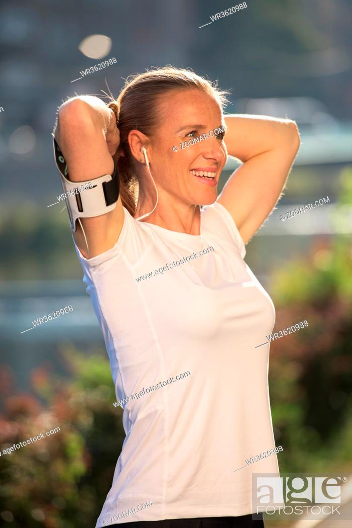 Stock Photo: portrait of jogging woman before running on early morning with sunrise in background.
