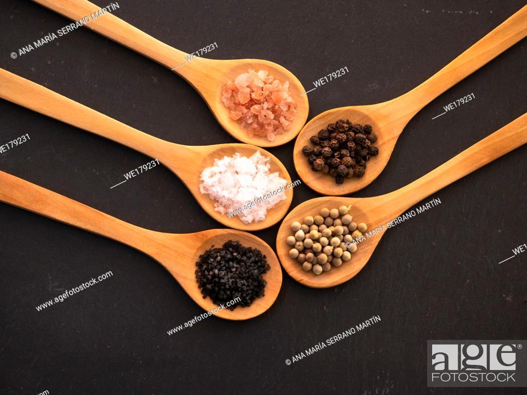 Stock Photo: Wooden spoons with himalayan salt, black hawaii salt, common salt, salt flakes and peppercorns on a slate plate.