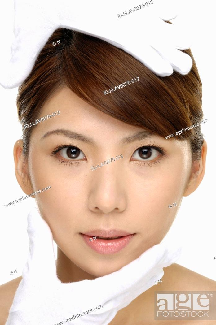 Stock Photo: Portrait of young beautiful woman touching her face isolated on white background.