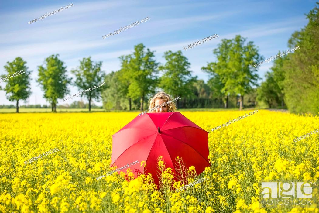 Stock Photo: Mature woman with red umbrella standing amidst oilseed rapes against sky.
