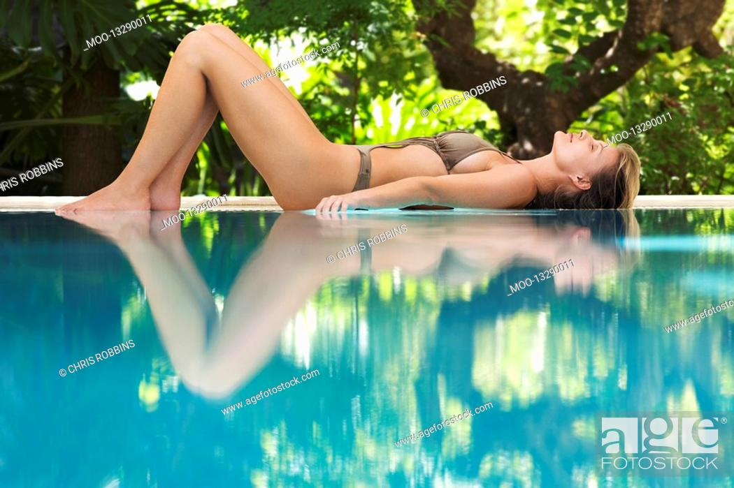 Stock Photo: Young woman lying by swimming pool portrait profile.