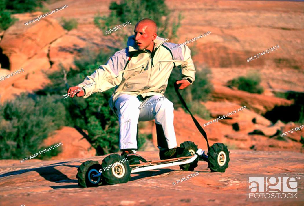 Stock Photo: Young man mountain boarding.