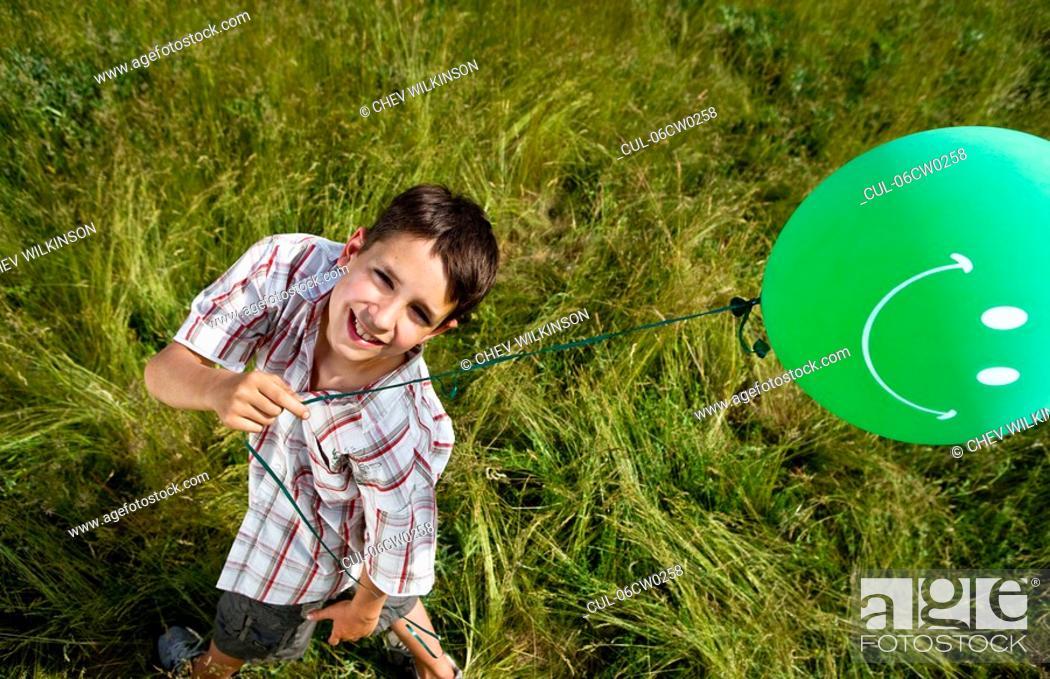 Stock Photo: Boy holding balloon, elevated.