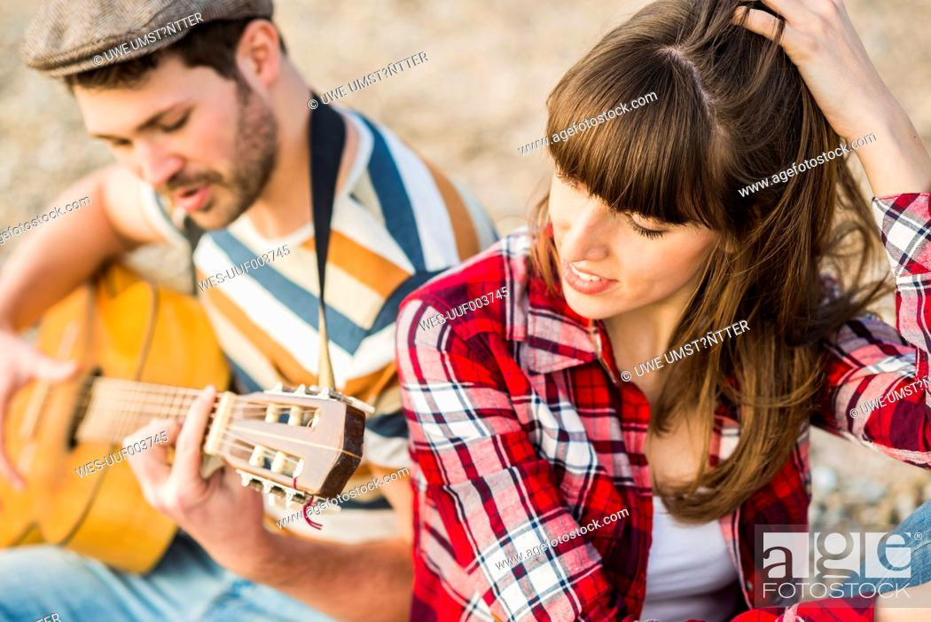 Imagen: Couple sitting by the riverside, playing guitar.