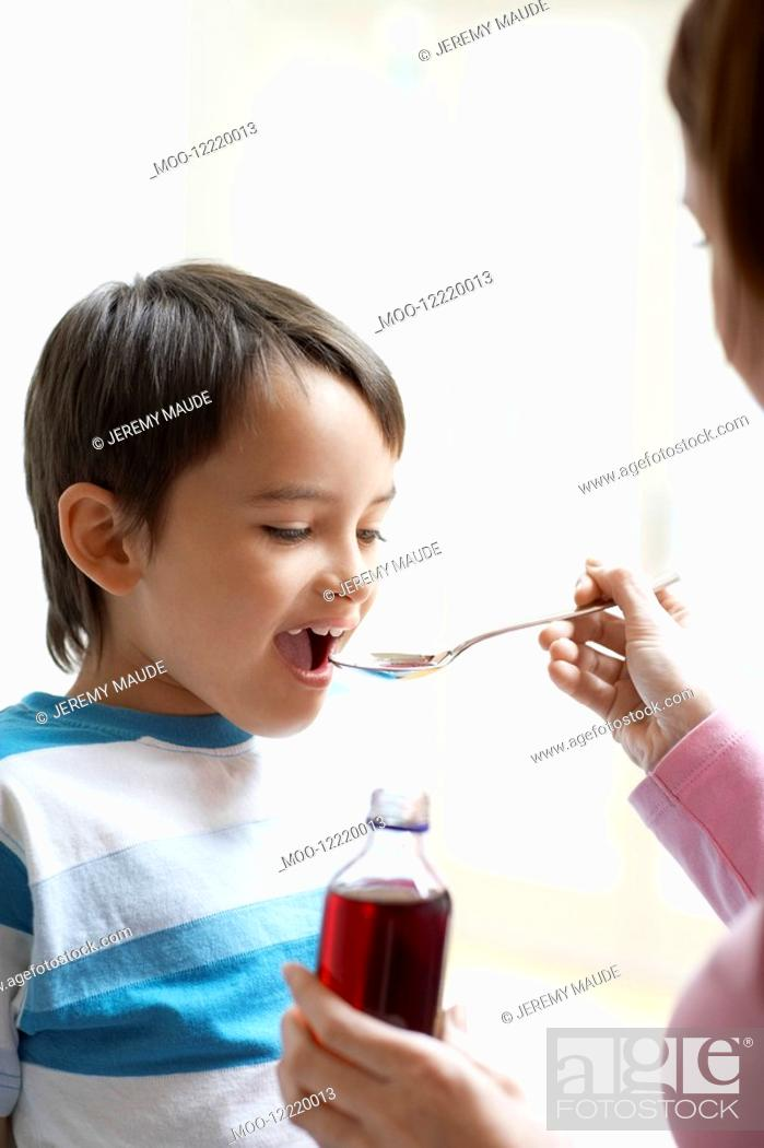 Stock Photo: Mother Giving Son Cough Syrup.