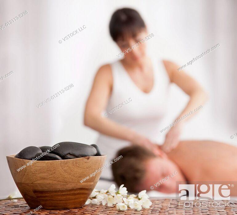 Imagen: Man receiving massage, stones in bowl in foreground.