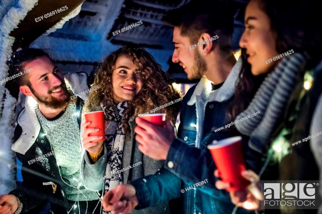 Stock Photo: A group of young friends outdoors in snow in winter at night, holding sparklers.