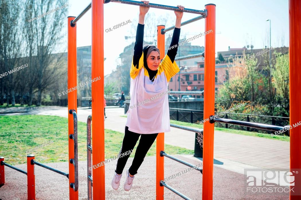 Stock Photo: Calisthenics class at outdoor gym, young woman swinging from exercise equipment.
