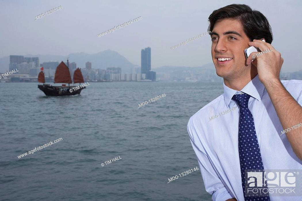 Stock Photo: Young business man talking on mobile traditional Chinese junk boat in background.