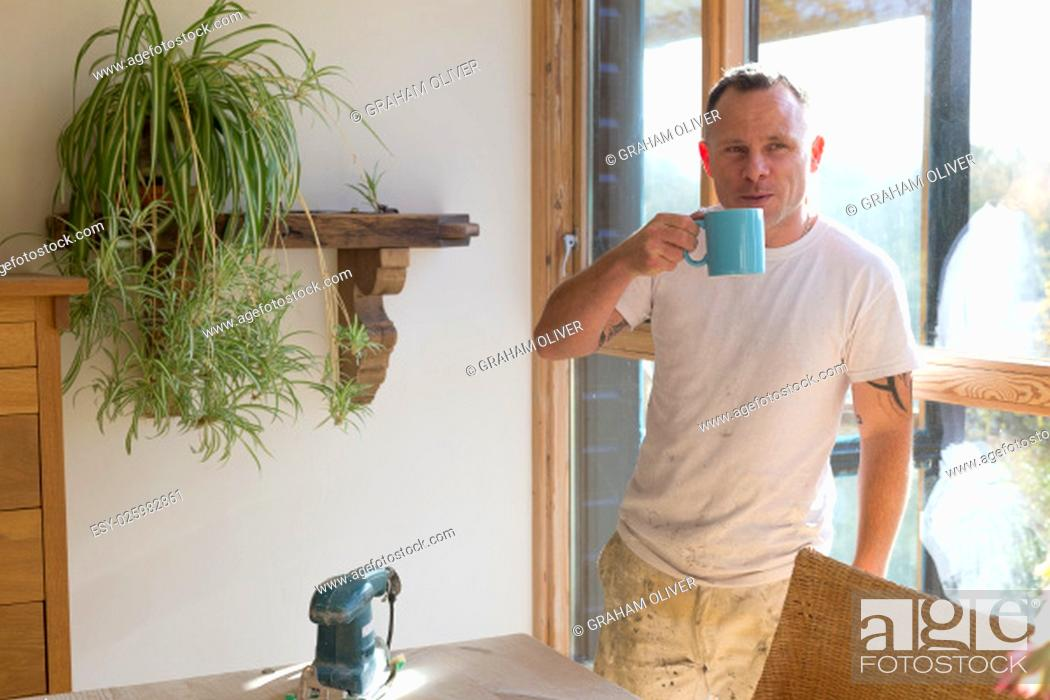 Stock Photo: Wood joiner having a break from work and enjoying a cup of tea in the sunshine.