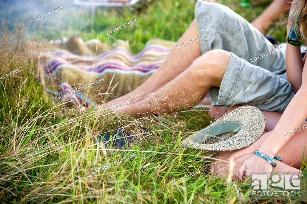 Stock Photo: Young couple sitting on the grass, close-up of legs.