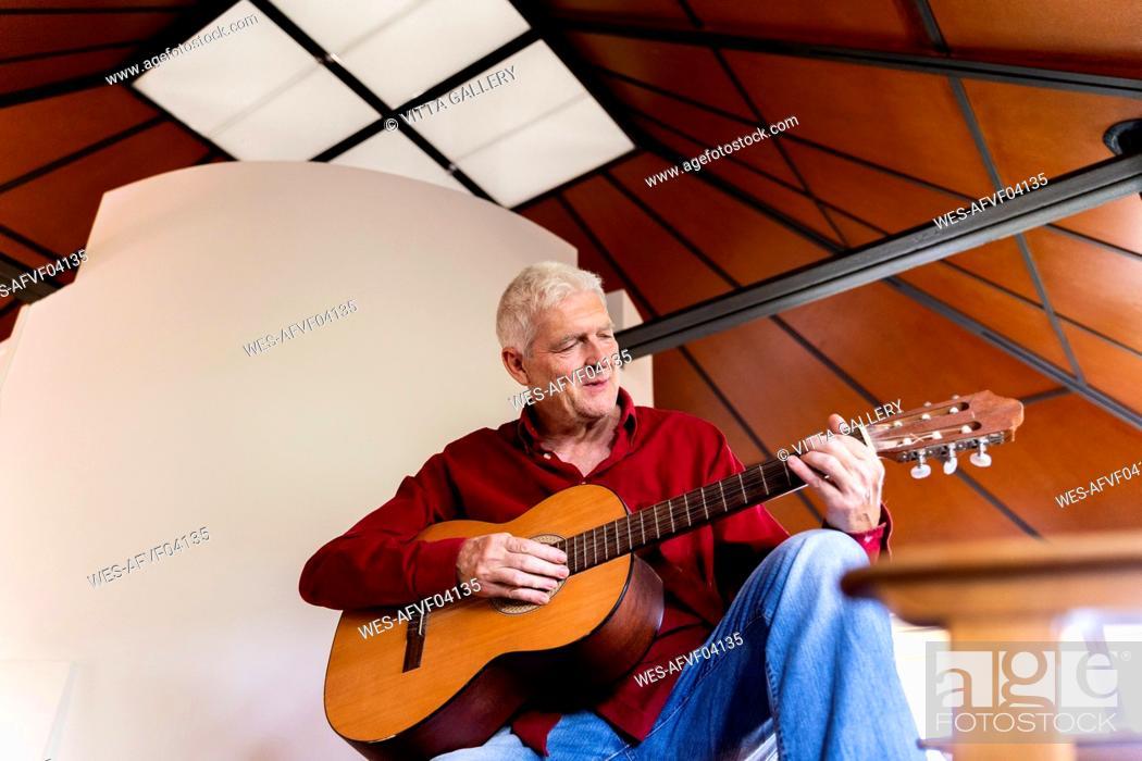Stock Photo: Senior man playing guitar at home.
