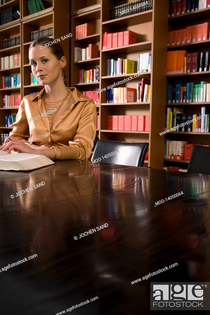 Stock Photo: Young woman with book at desk in library portrait.