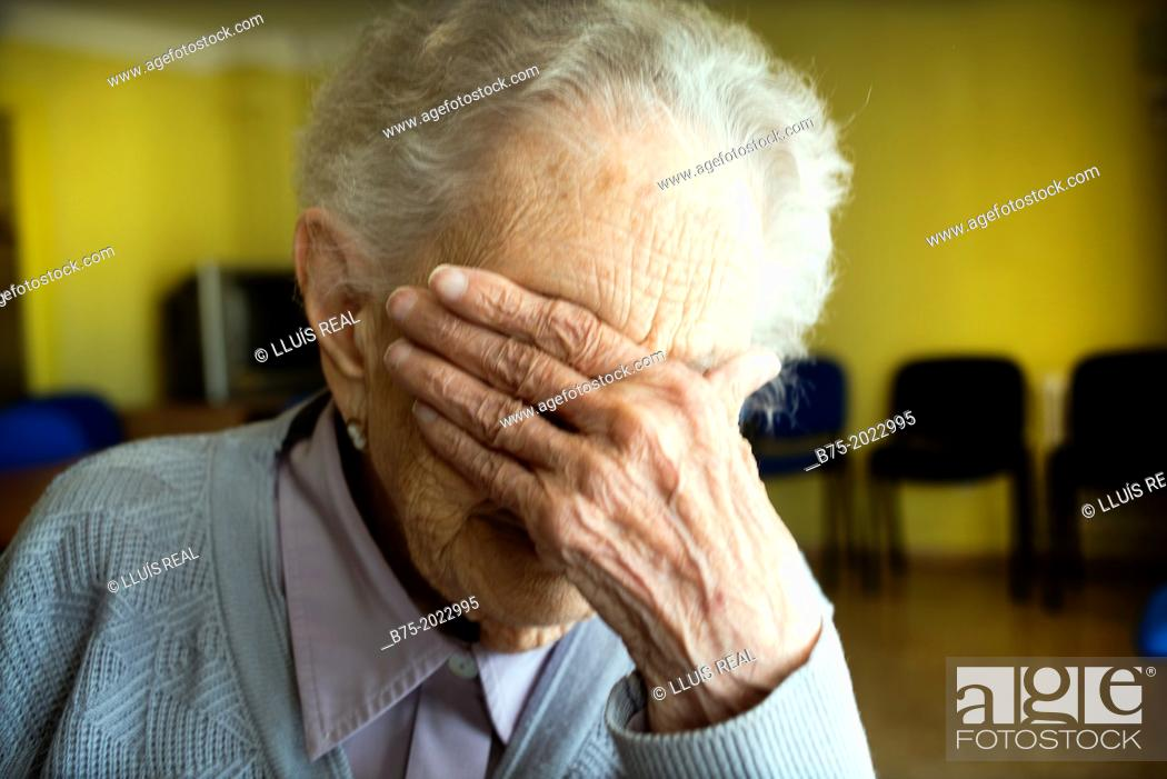 Photo de stock: Portrait of a centennial woman in a elderly people home, hand covering her face.