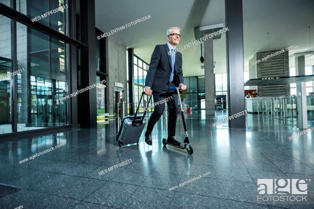 Stock Photo: Germany, Stuttgart, Businessman using scooter while pulling luggage in office building.