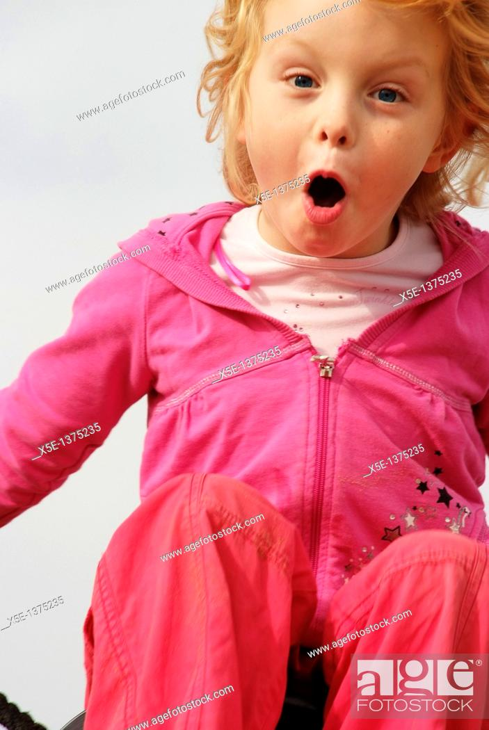 Stock Photo: Happy 7 year girl leaping in air in childrens playground.