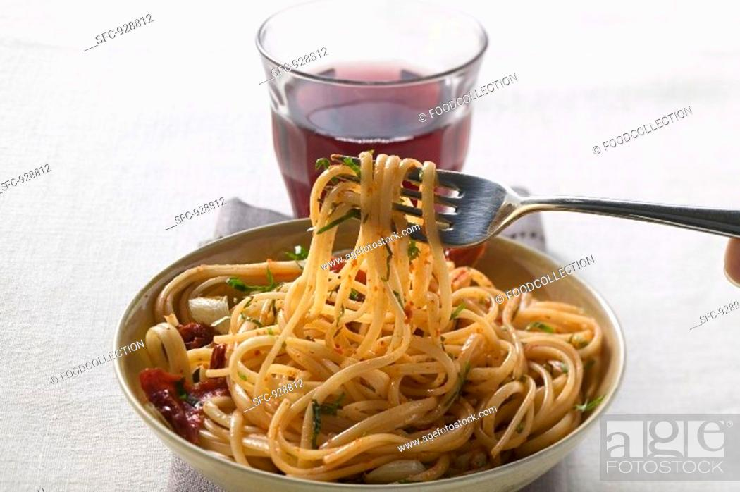 Stock Photo: Spaghetti with dried peppers, glass of red wine.