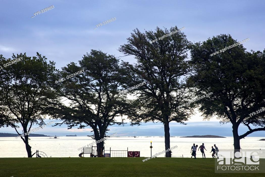 Stock Photo: Kids playing football in Willows Park in Oak Bay- Victoria, Vancouver Island, British Columbia, Canada.