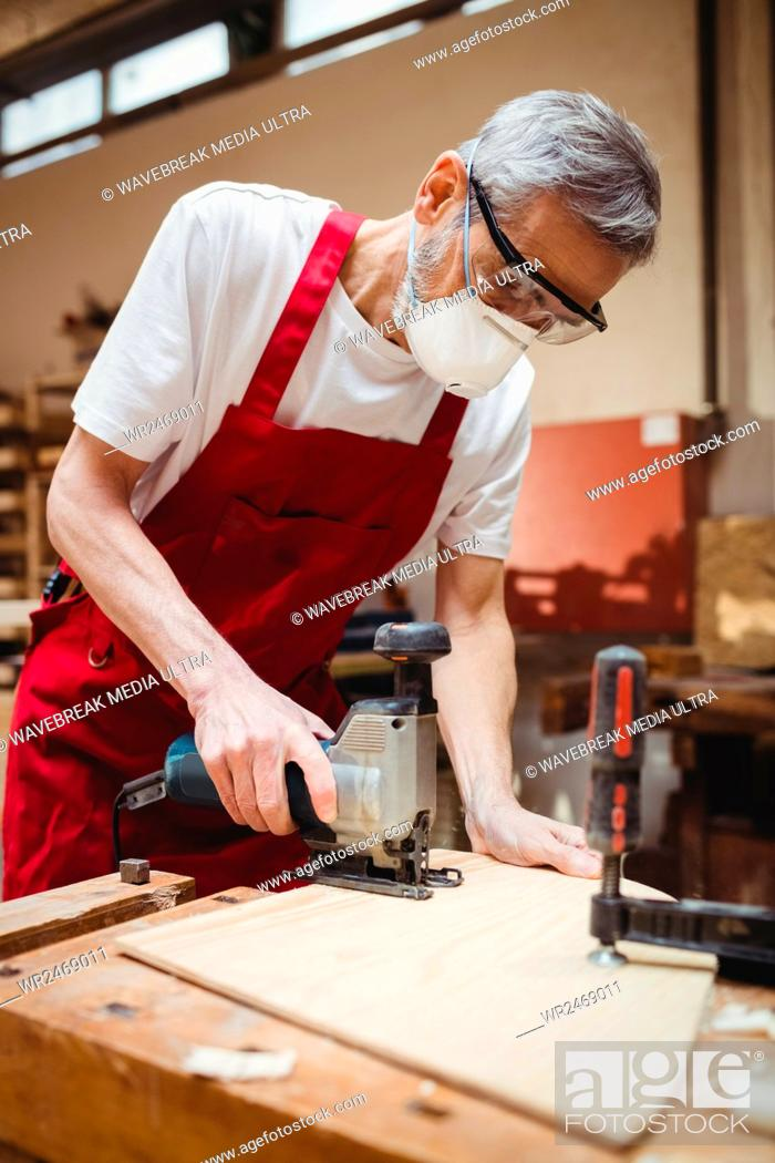 Stock Photo: Carpenter cutting a plank of wood in carpentry.