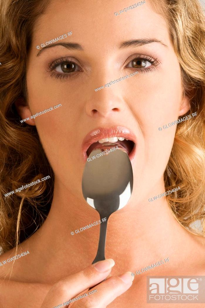 Stock Photo: Portrait of a young woman with a spoon in her mouth.
