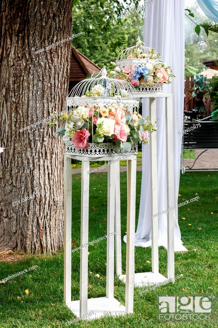 Imagen: Wedding ceremony decorations bouquets of roses and eustoma in restaurant outdoors.