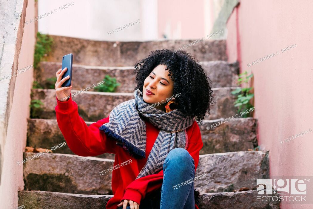 Stock Photo: Young woman taking selfie on steps.