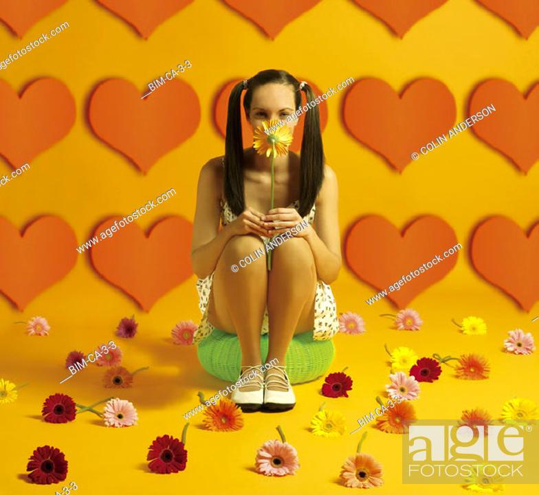 Stock Photo: Woman sitting holding flower.
