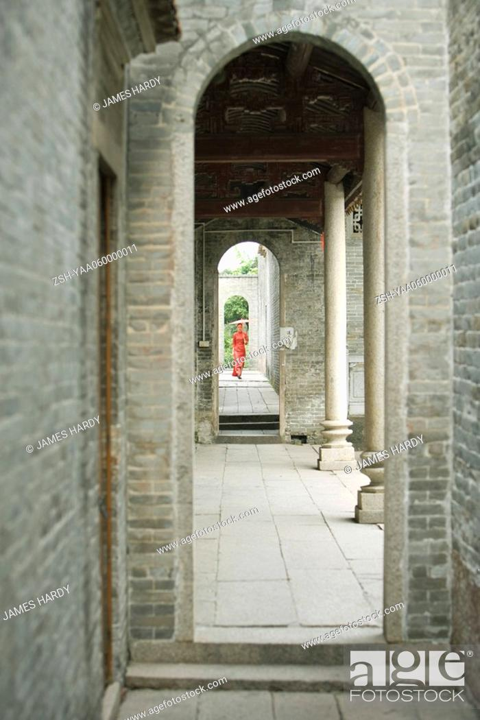 Stock Photo: Young woman in traditional Chinese clothing, seen through archway.