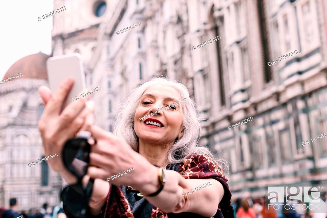 Stock Photo: Stylish mature woman taking smartphone selfie in Florence, Italy.