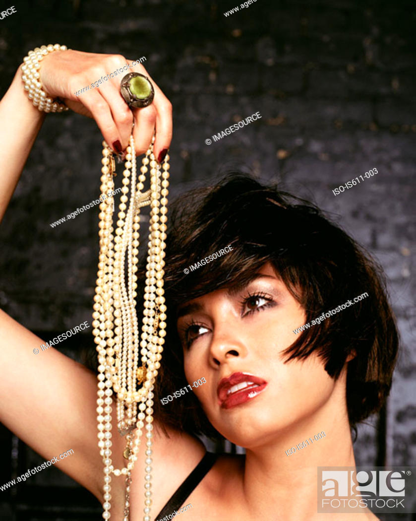 Stock Photo: Young woman holding pearl necklaces.