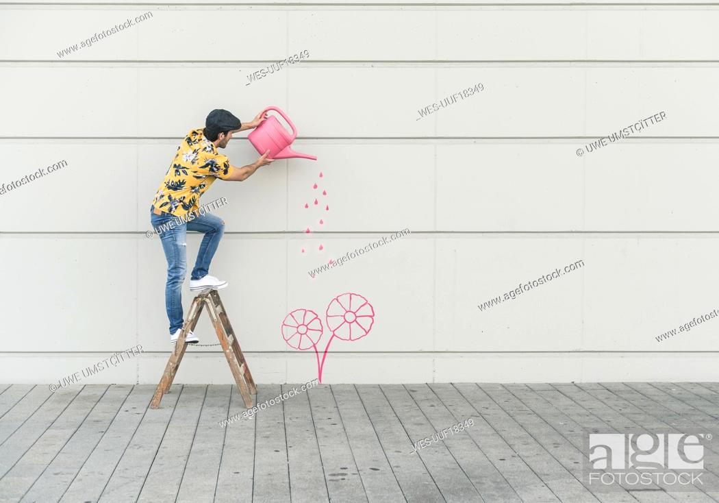 Stock Photo: Digital composite of young man watering flower at a wall.