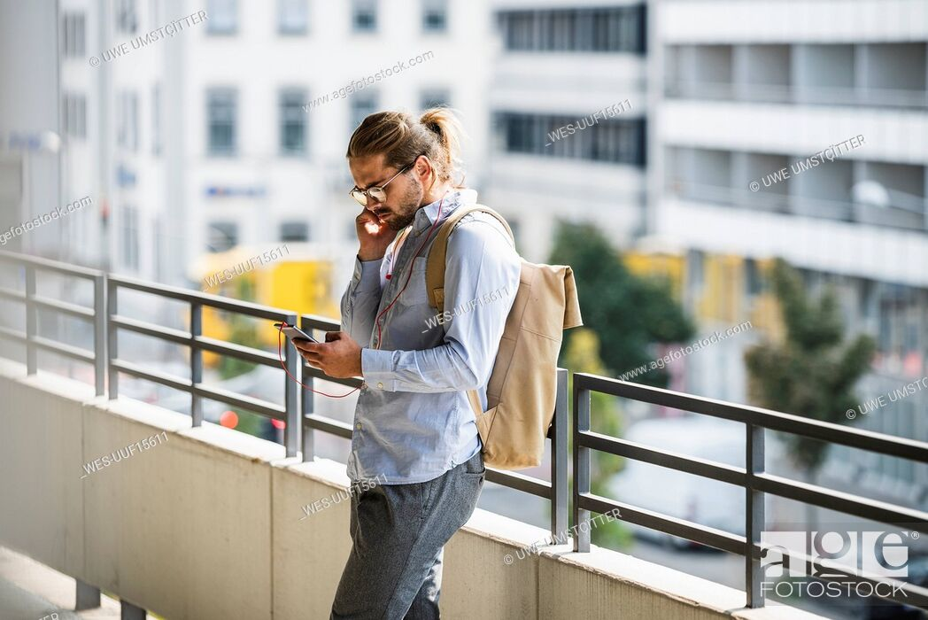 Stock Photo: Young businessman with backpack, standing in parking garage, using smartphone.