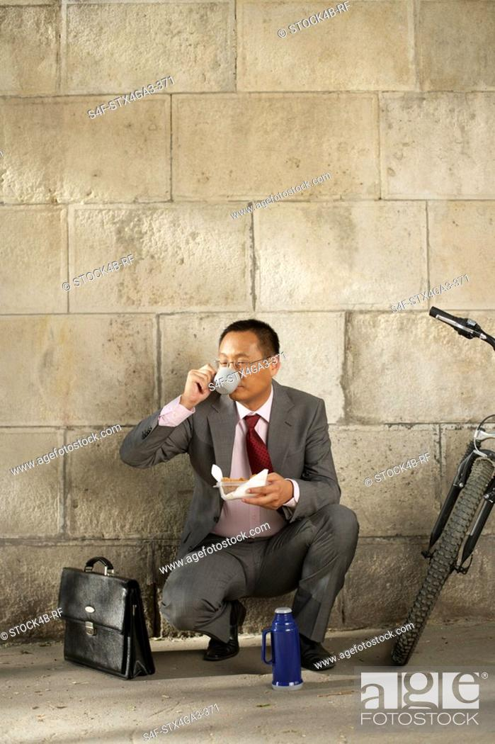 Stock Photo: Businessman drinking coffee in crouched position.