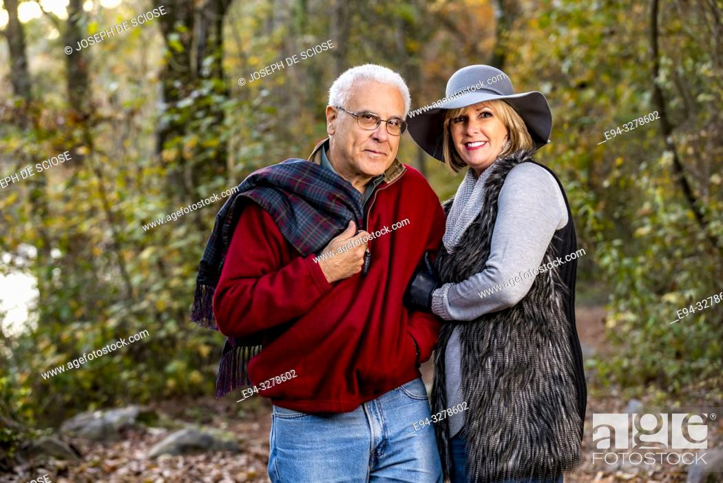 Stock Photo: A happy 65 year old man and a 59 year old blond woman walking together in a forest setting, smiling at the camera.