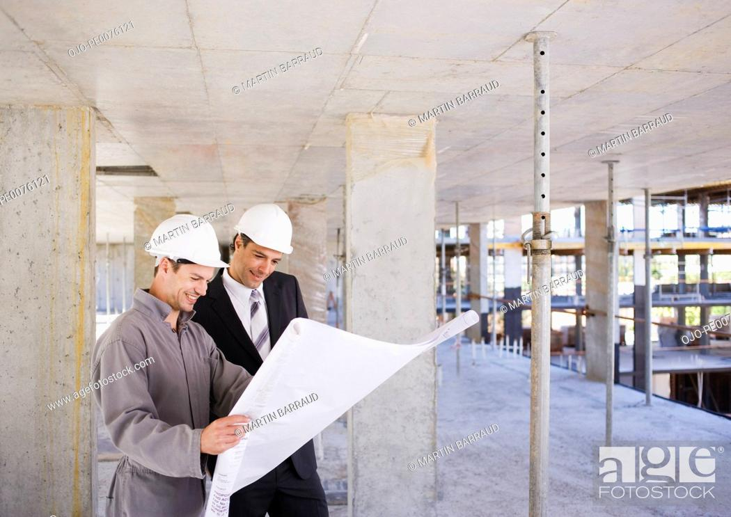 Stock Photo: Construction workers looking at blueprints on construction site.