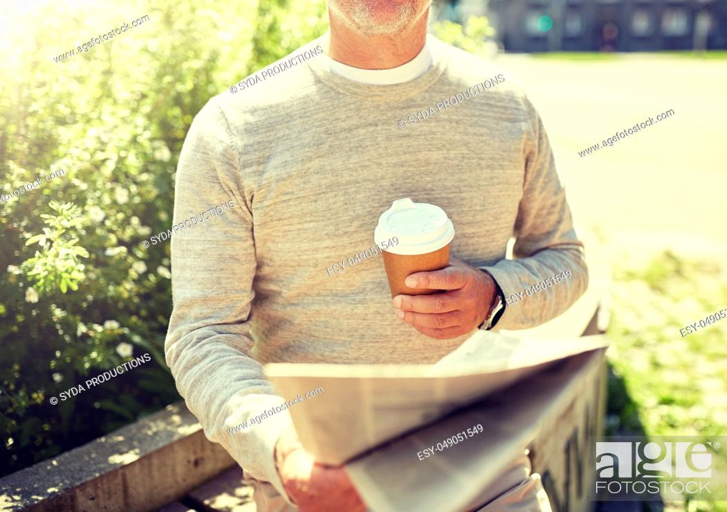 Stock Photo: senior man with coffee reading newspaper outdoors.