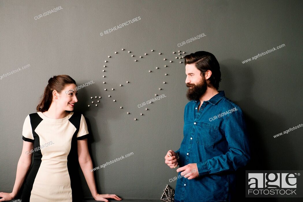 Stock Photo: Young couple by wall with heart shape.