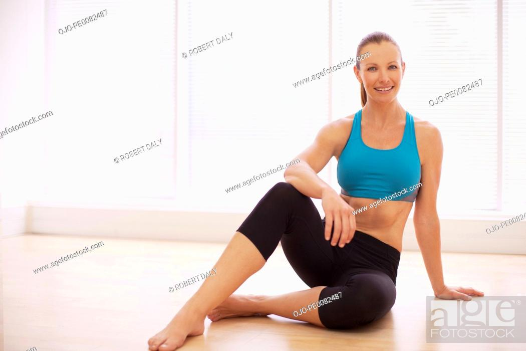 Stock Photo: Portrait of smiling woman in sports bra sitting on floor.