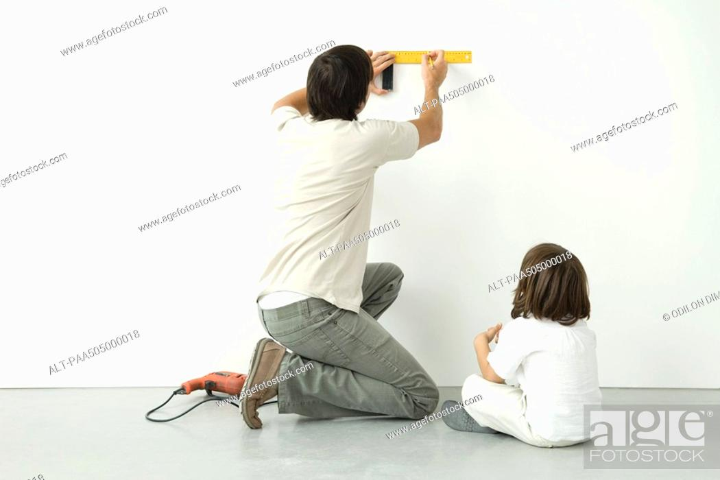 Stock Photo: Man measuring wall with a ruler while his son watches, drill on the floor nearby.