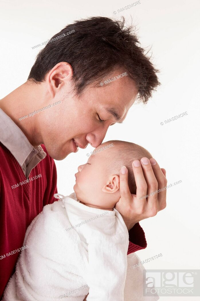 Imagen: Man holding baby girl with smile and looking down.