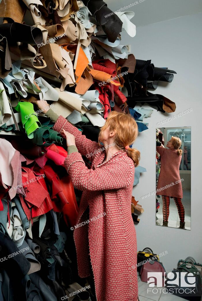 Stock Photo: Woman making selection from stack of leather skins.