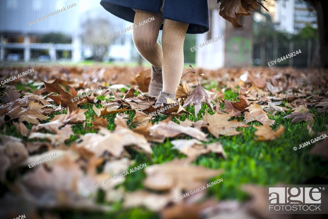 Imagen: Child girl walking over fallen leaves carpet at park. Autumn and kids concept.
