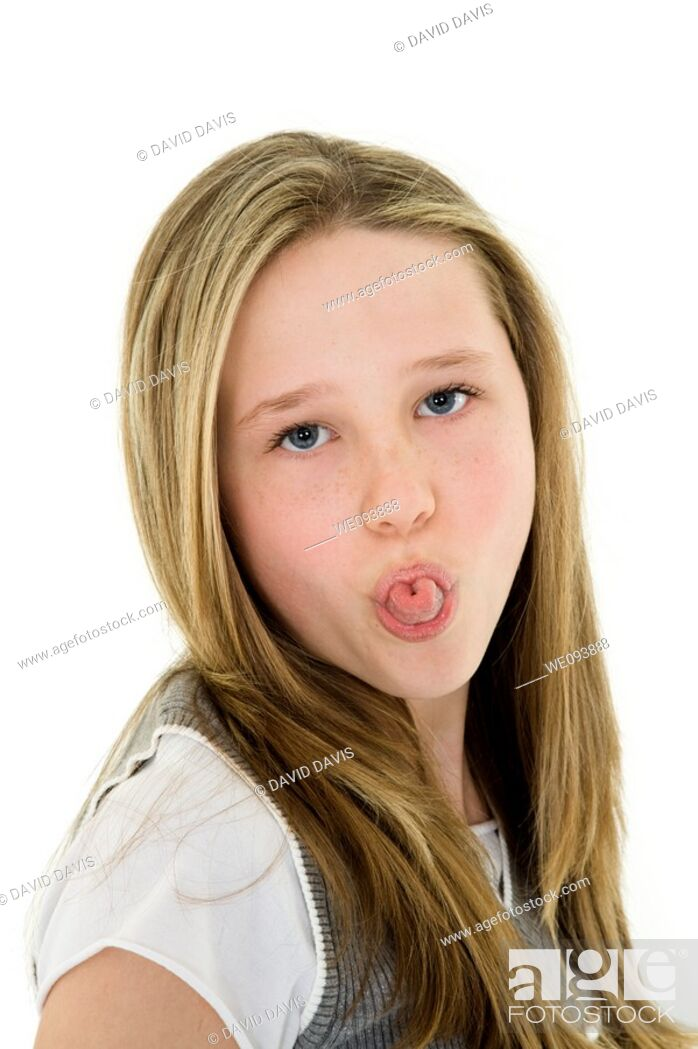 Stock Photo: Caucasian preteen girl displaying some attitude by sticking out her tongue.
