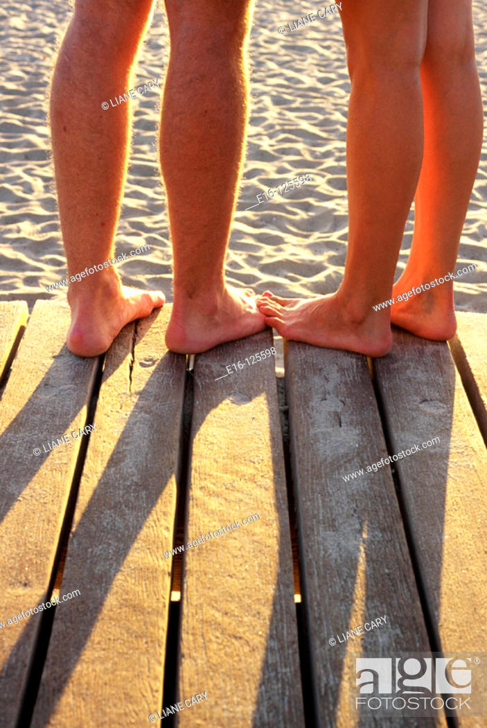 Stock Photo: Couple's feet together at beach boardwalk.