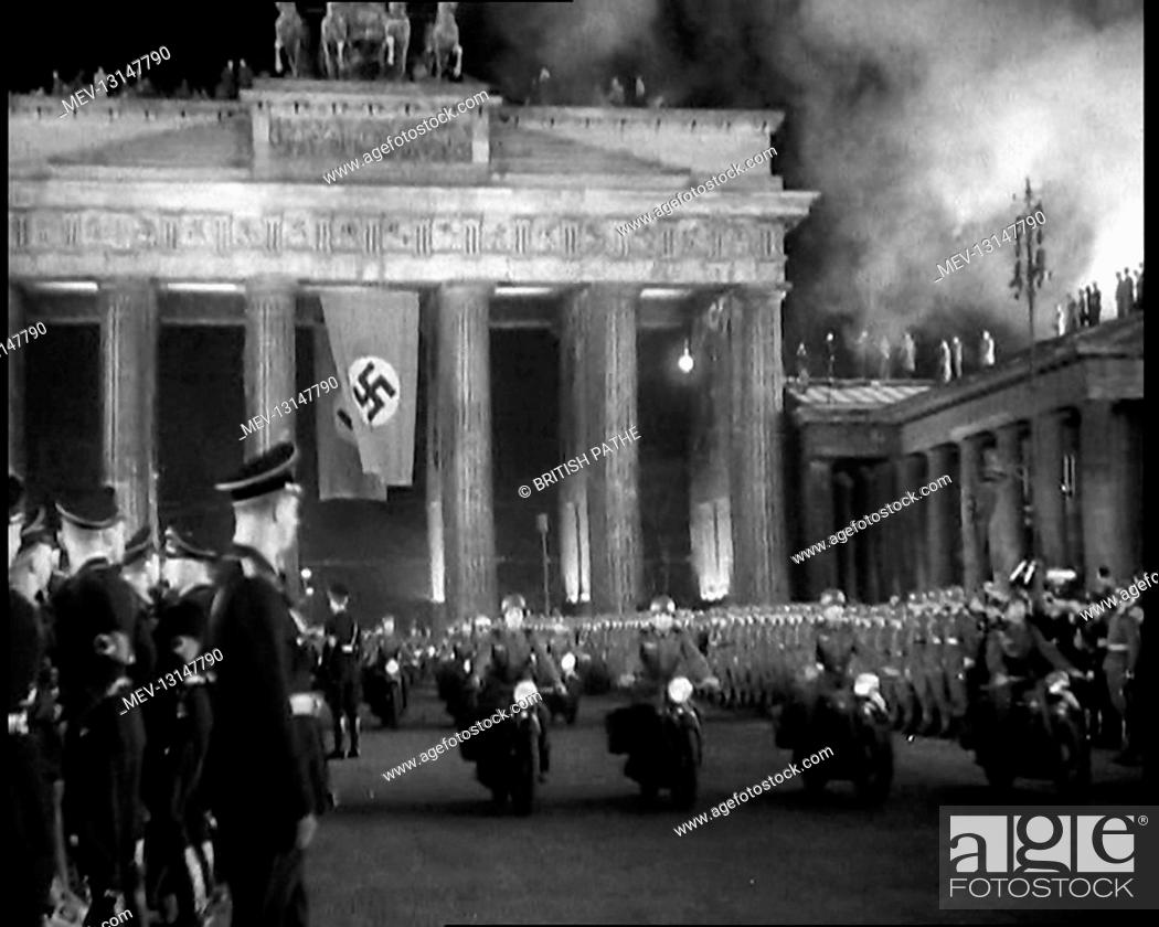 Stock Photo: Male German Officers and Soldiers Lining Pariser Platz by the Brandenburg Gate With A German Flag Hanging From It as a Formation of Male Motorbike Riders Pass.
