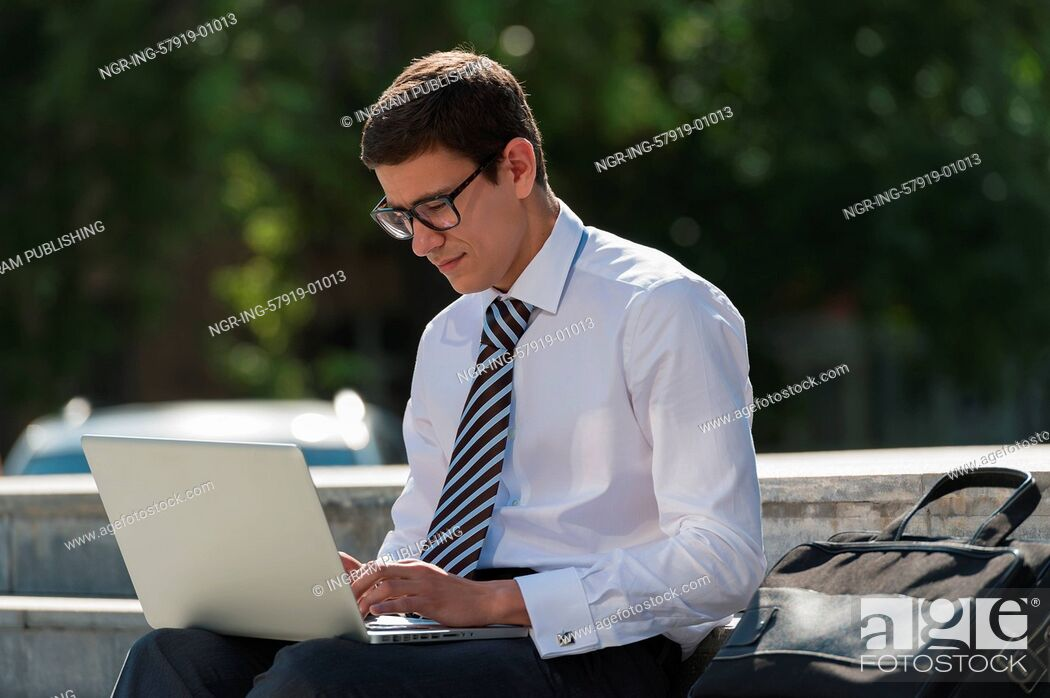 Stock Photo: Man with laptop at summer park on bright day.