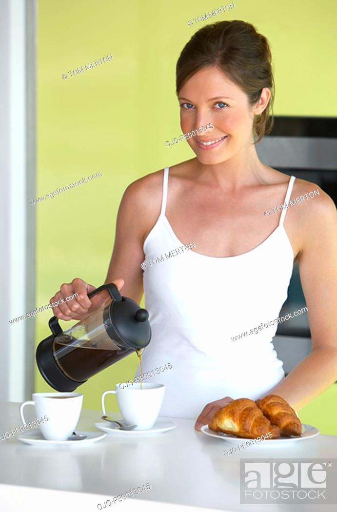 Stock Photo: Woman in kitchen with coffee and croissants smiling.